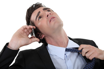 businessman talking on the phone and taking off his tie