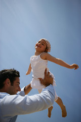 Father lifting his daughter against a blue sky