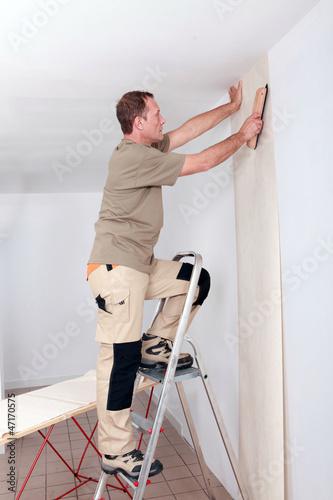 Handyman laying wallpaper