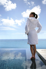 Woman stood by swimming pool in bathing robe