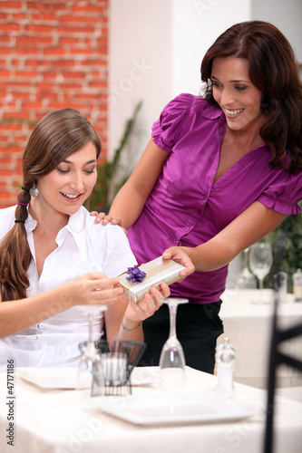 a teenage girl receiving a gift at restaurant