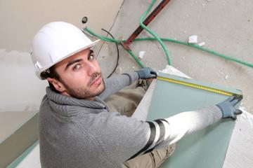 Man measuring plaster-board