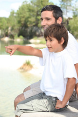 Father and son sitting by a lake
