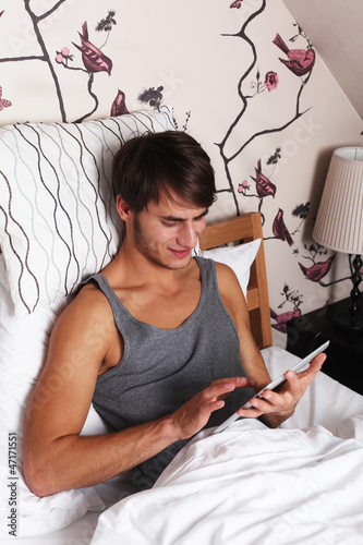 Young Man in Bed with a Tablet PC