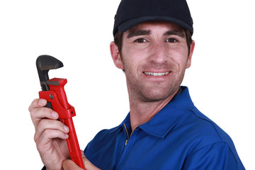 A manual worker holding a wrench.