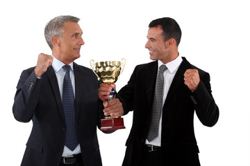 Successful businessmen holding a gold cup