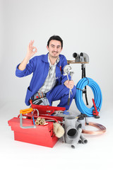 Plumber surrounded by equipment