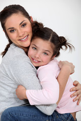 Closeup of a young woman hugging a little girl