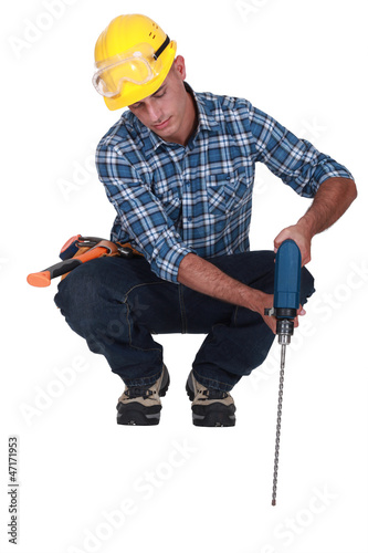 Man drilling into floor
