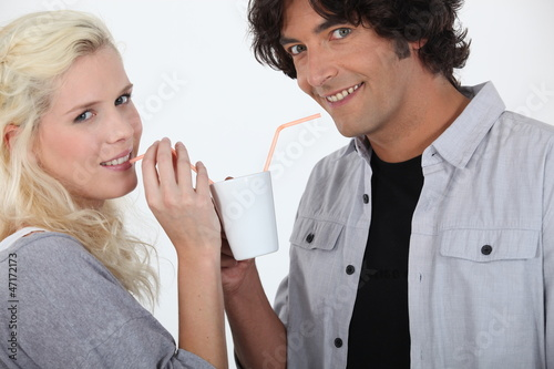 couple drinking together off same mug with straw