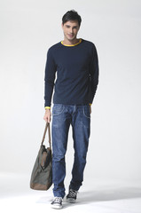 Full length young Casual man with bag posing in the studio