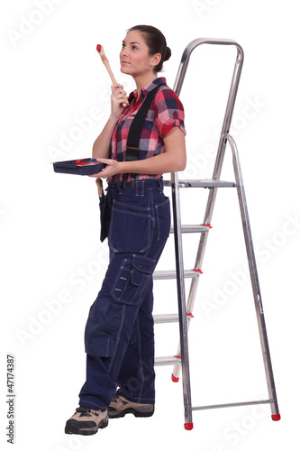 Young woman stood by ladder with paint brush