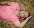 Good looking, fit male model relaxing laid down in a field