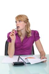 Pensive secretary sucking pen