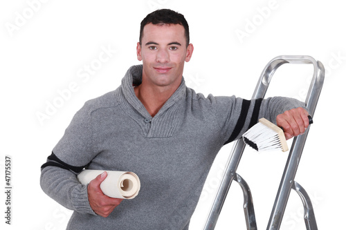 Man with roll of wallpaper and step ladder