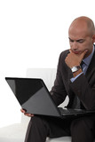 Pensive bald man using laptop