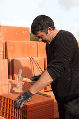 Builder shaping a brick