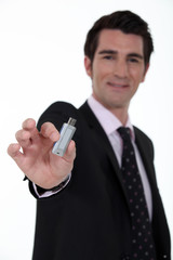 A businessman handing a USB key.