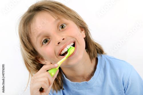 Portrait d'enfant blond se brossant les dents