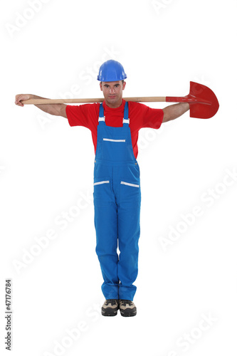 A construction worker with a shovel in a religious stance.