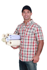 Man with rolls of wallpaper