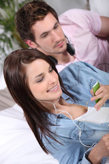 Couple in bed with music player
