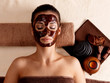 woman relaxing with facial mask on face at beauty salon
