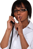 Woman talking on the phone and holding her finger to her lips