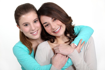 Two young women in a friendly hug