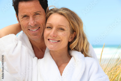 Happy couple wearing dressing gowns at the beach