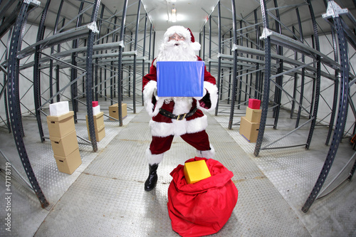 Santa Claus preparing for Christmas,showing gift