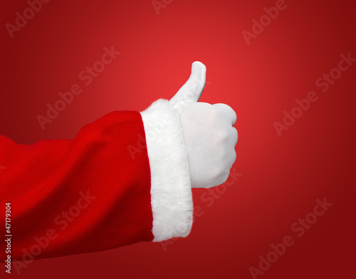 Santa Claus hand showing thumbs up over red background
