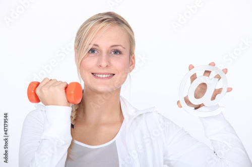 Young woman holding at sign and dumbbell