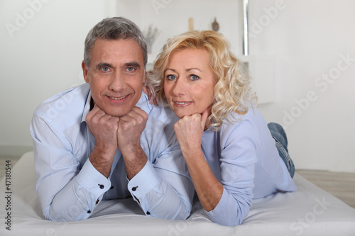 Man and woman lying with their heads propped up on their hands
