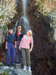 Three tourists near waterfall in the mountains, Ala-Archa, Kyrgy