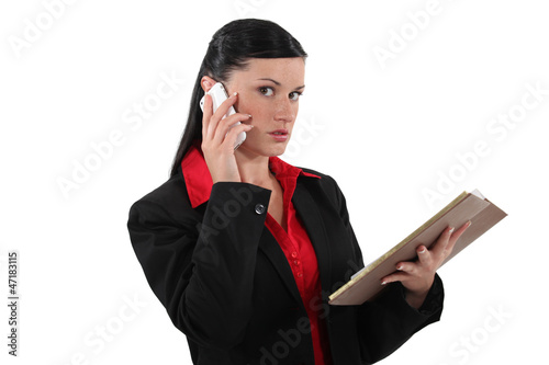 businesswoman talking on her cell and looking at her agenda