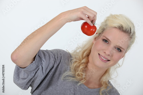 Smiling blond woman holding tomato on white background