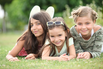 Three young girls lying on the grass