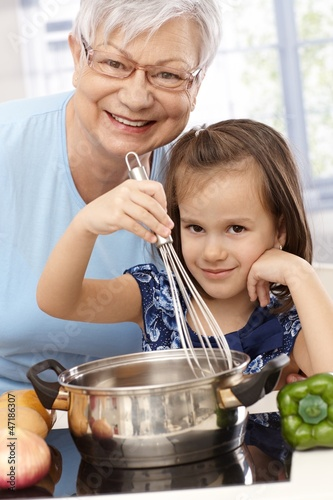 Granny and granddaughter cooking smiling