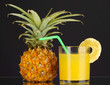 Ripe pineapple and juice glass isolated on black