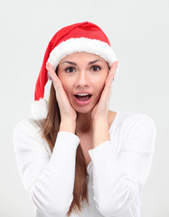 surprised christmas woman wearing a santa hat smiling isolated
