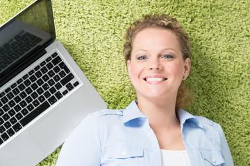entspannte frau mit computer liegt auf einem grünen teppich