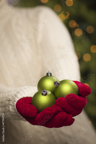 Woman Wearing Seasonal Red Mittens Holding Green Christmas Ornam