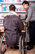 Rollstuhlfahrer beim shoppen mit Hilfe