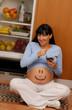 Divertida mujer embarazada comiendo chocolate en la cocina.