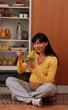 Divertida mujer embarazada comiendo ensalada en la cocina.