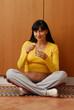 Divertida mujer embarazada comiendo yogurt en la cocina.