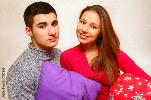 Smiling boy and girl with Christmas pillows isolated on white ba