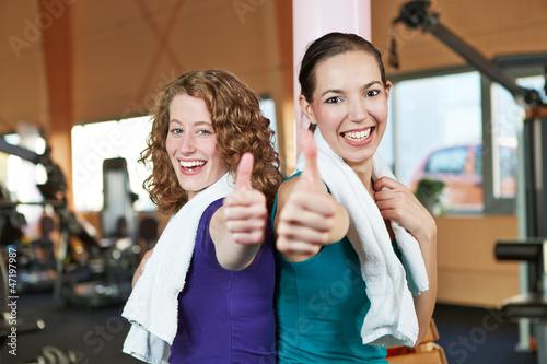 Frauen im Fitnesscenter halten Daumen hoch