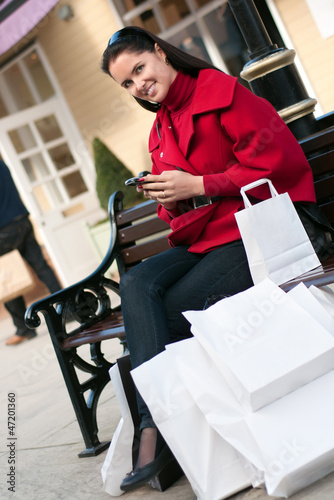 Happy smiling woman sitting on the bench after shopping